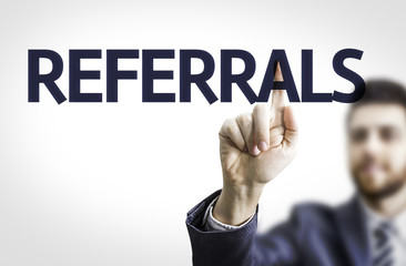 Business man pointing to transparent board with text: Referrals