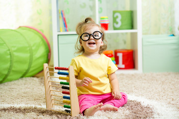 child weared glasses playing with abacus