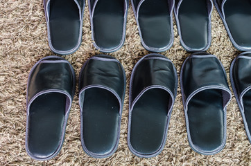 row of black slippers on carpet