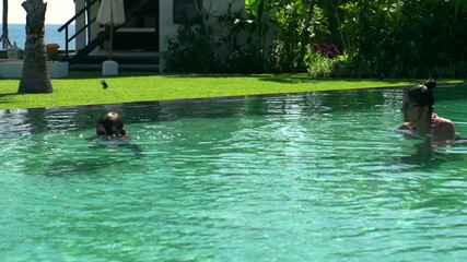 Mother and her son having fun while diving in the swimming pool