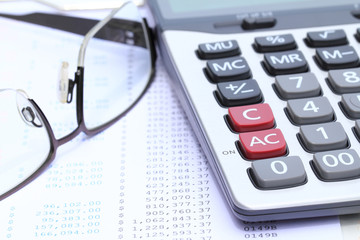 Calculator and eye glasses on bank statement