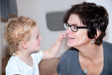 Woman putting cream on a playful child