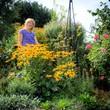 Frau im spätsommerlichen Garten mit Blumen