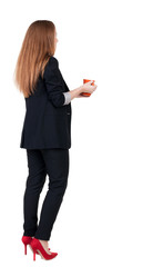 Rear view of a young business woman drinking coffee or tea while