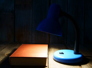 The fixture and the book. On wooden background.