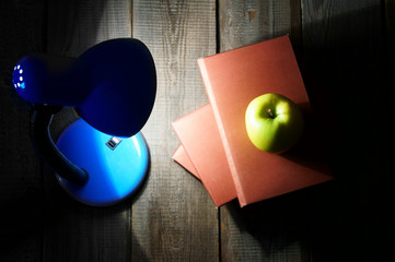 Books, an apple and the fixture. On wooden background.