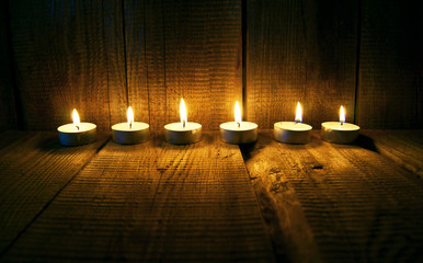 Burning candles. On wooden background.