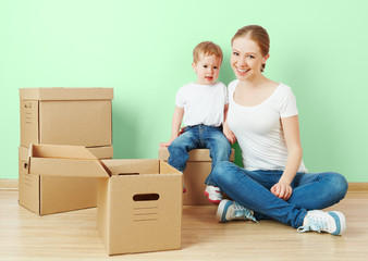 happy family mother and daughter in apartment with boxes