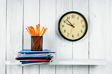 Watches, writing-books and school tools on a wooden shelf.