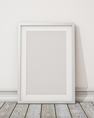 blank white picture frame on the white wall and the wooden floor