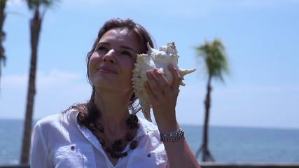 Woman holding big shell and enjoying it, slow motion shot