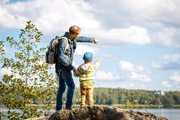 Young father is hiking with 3 year old son