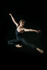 young ballet dancer dansing on black background