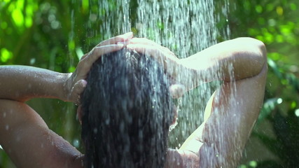 Woman showering hair and refreshing in the garden, slow motion