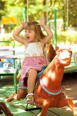 Happy beautiful girl on a merry-go-around
