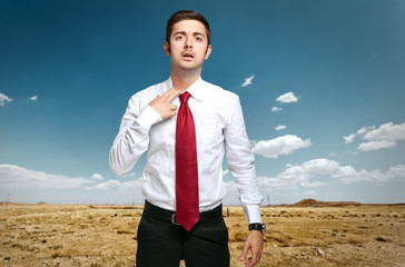 Fired businessman sweating in the desert
