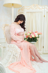 Pregnant in  tender peach dress sits on chair