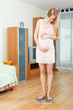 pregnancy woman standing on bathroom scales