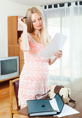 Long-haired pregnant woman looking  document