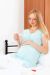pregnant woman holding thermometer