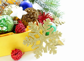 Christmas decorations (balls, cones, stars) in the yellow box