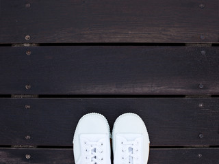 standing on the wooden floor in white shoes