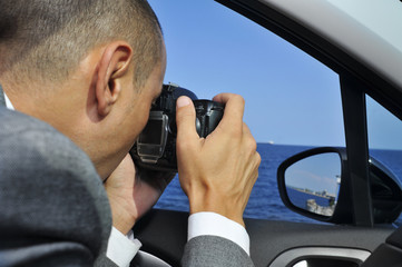detective or a paparazzi taking photos from inside a car