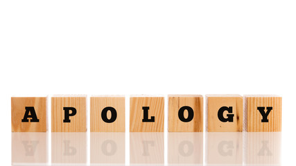 The word Apology on seven wooden cubes