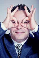 Businessman making binoculars with his hands