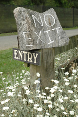 Entry, no exit wooden sign with fading letters
