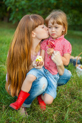 Young woman kissing her little daughter