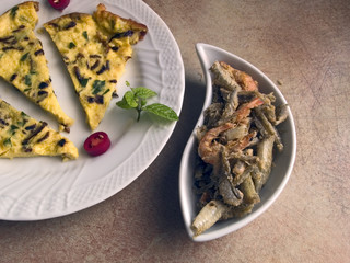 Italian cuisine - omelette with onions and herbs, and fried fish