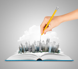 Hand drawing a city on an open book