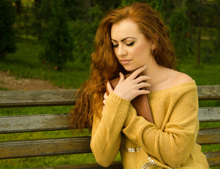 Ginger-haired woman sitting on a bench with book