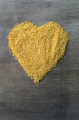 millet grains formed in heart shape on wooden background