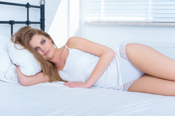 Beautiful young blond woman relaxing in bed