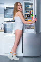 Hungry young woman snacking out of the fridge