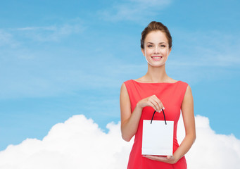 smiling elegant woman in dress with shopping bag