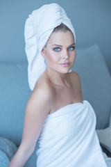 Young Woman in White Bath Towel Sitting on Sofa