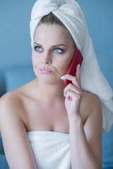 Thinking Woman in Bath Towel with Red Cell Phone