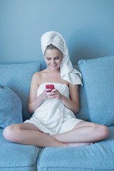 Young Woman Wearing Bath Towel with Red Cell Phone