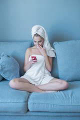 Woman in Bath Towel with Cell Phone on Sofa