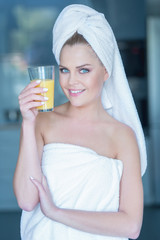 Lady in towel holding glass of juice