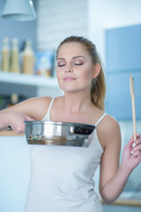 Young woman savoring the smell of her cooking