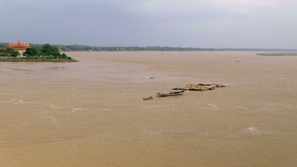 Convoy of bamboo move slowly on the mekong river (1)