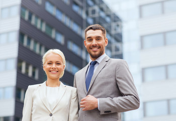 smiling businessmen standing over office building