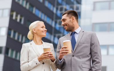 smiling businessmen with paper cups outdoors