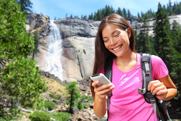 Smartphone - woman hiker using smart phone on hike