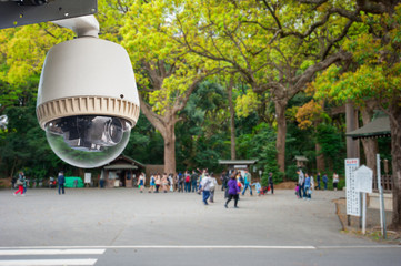 CCTV Camera or surveillance operating in outdoor park with peopl