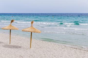 Straw umbrellas on sand beach.